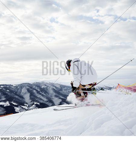 Male Skier In Winter Jacket Sliding Down Snow-covered Slopes On Skis. Man Freerider In Helmet Skiing