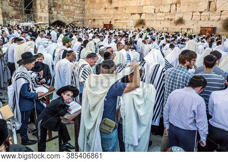 JERUSALEM, ISRAEL - SEPTEMBER 26, 2018: The blessing of the Cohanim. Solemn ceremony on the Western wall of the Temple. Jews praying wrapped in white Talit. The concept of religious and photo tourism