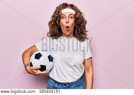 Middle age beautiful sporty woman playing soccer holding football bal over pink background scared and amazed with open mouth for surprise, disbelief face