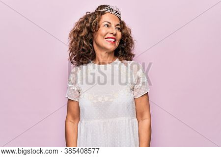 Middle age brunette woman wearing cute princess crown tiara over pink background looking to side, relax profile pose with natural face and confident smile.