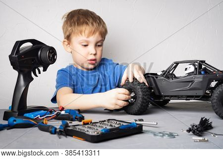 Radio Controlled Models: A Little Boy In A Blue T-shirt Is Repairing His Rc Car Buggy.