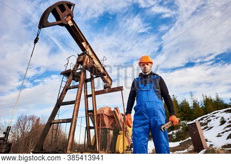 Portrait Of Oil Well Enginner In Protective Helmet And Work Overalls Holding Industrial Wrench. Male
