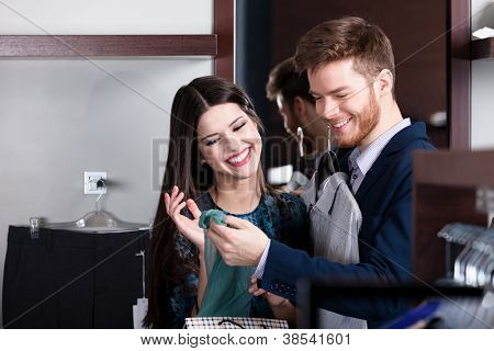 Beautiful couple looks at purchases in the shop