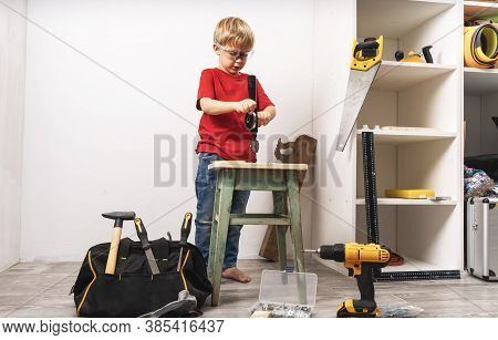 A Boy Works In A Hand Drill And Repairs Furniture