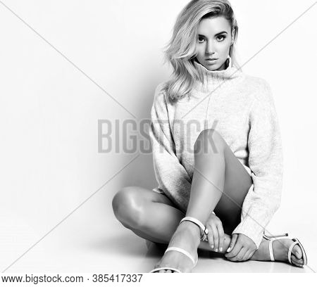 Portrait Of Young Sexy Blonde Woman Model In Warm Sweater And High Heel Shoes Sitting On Floor And L