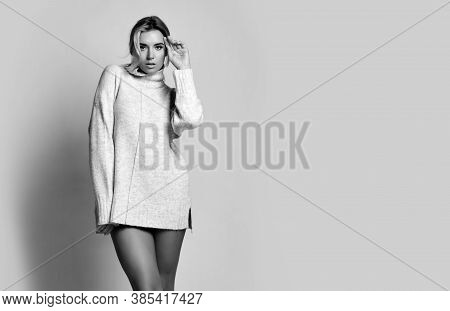Young Sexy Beautiful Woman In Long Knitted Sweater Standing, Showing Perfect Legs And Posing Over Wh