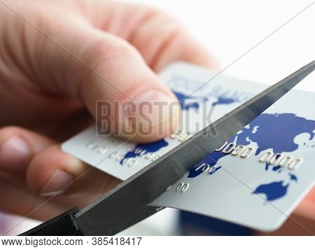 Close-up Of Male Hands Holding Plastic Card And Cutting In Half With Scissors. Businessman Changing
