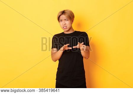 Portrait Of Disgusted Picky Asian Guy, Refusing And Grimacing, Standing Yellow Background