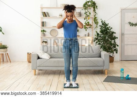 Weight Gain. Unhappy Black Girl Standing On Scales Touching Head Having Excess Kilograms Posing Indo