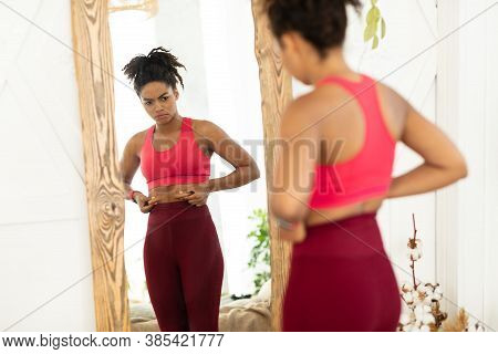 Unhappy African American Woman Touching Fat Belly Standing Near Mirror, Gaining Kilograms And Not Lo