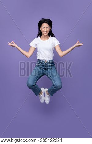 Positive Young Lady Jumping Meditating In Mid-air Posing Over Purple Background In Studio, Smiling L