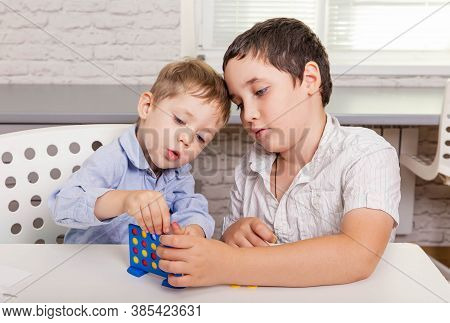 Two Funny Brothers Are Laughing And Playing A Board Game Together On The Desk At Home. Happy Childre