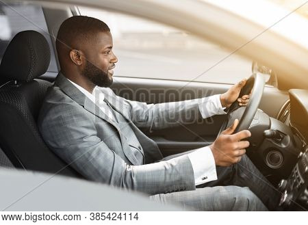 Side View Of Happy African American Man In Expensive Suit Driving Car. Excited Young Black Entrepren