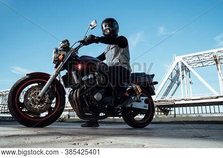 Man Seat On The Motorcycle.motorcyclist In Black Helmet On A Red Bike