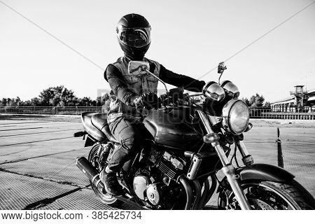 Man Rides A Motorcycle In The City.motorcyclist Riding A Bike During The Day On The Road.black And W