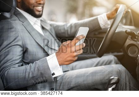 Black Guy In Suit Using Smartphone While Driving Car. Unrecognizable African American Businessman Ch