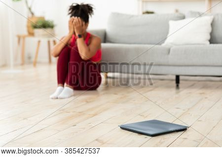 Weight Loss. Desperate African Woman Crying Sitting Near Scales Gaining Weight At Home. Selective Fo