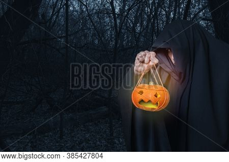 A Man In Black Clothes Holds A Jack-o-lantern, The Lantern Glows With Yellow Light In A Creepy Night