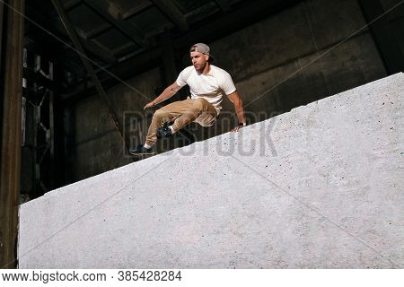 Young Sportsman Doing Parkour In City. Athlete Is Practicing Freerunning Outdoors On The Streets. Ar