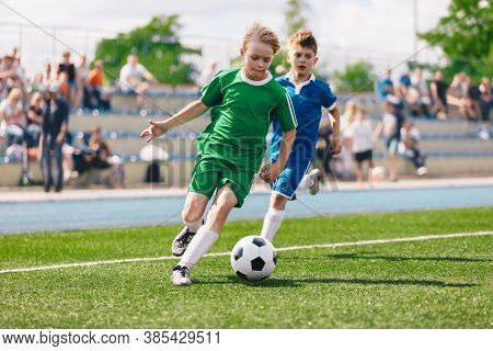 Young Boys Playing Soccer Game. Kids Having Fun In Sport. Happy Kids Compete In Football Game. Runni