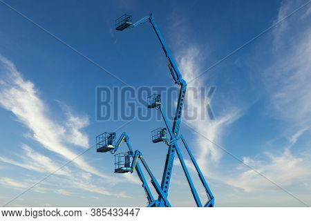 several blue hydraulic crane cherry picker against the sky