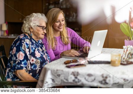 Adult granddaughter teaching her elderly grandmother to use laptop