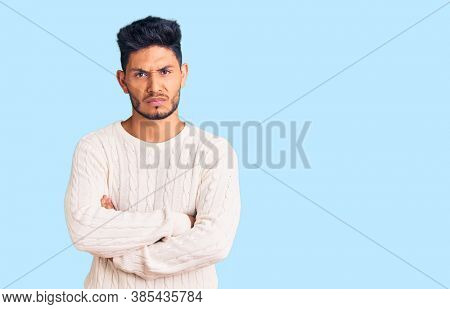 Handsome latin american young man wearing casual winter sweater skeptic and nervous, disapproving expression on face with crossed arms. negative person.