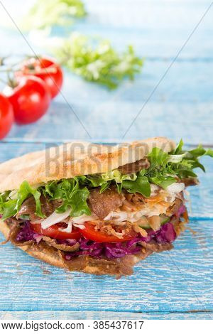 Turkish Doner Kebab Sandwich on wooden background, close-up.