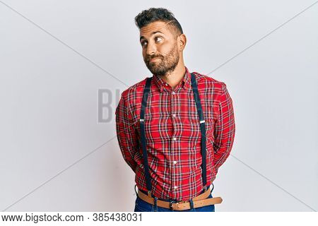 Handsome man with beard wearing hipster elegant look smiling looking to the side and staring away thinking.