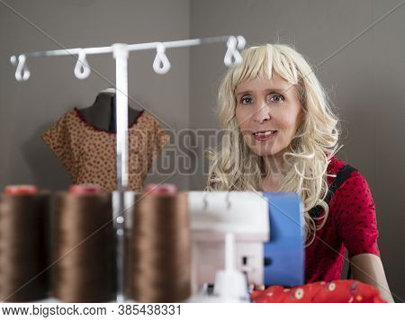 Horizontal Portrait Of A Smiling Caucasian Woman Dressmaker Sewing Fabric In Her Workshop