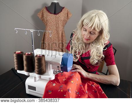 Horizontal Portrait Of A Caucasian Woman Dressmaker Sewing Fabric In Her Workshop