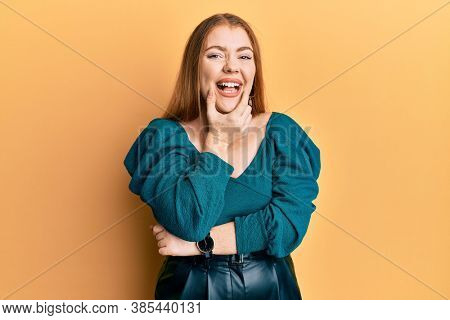 Young beautiful redhead woman wearing elegant and sexy look looking confident at the camera smiling with crossed arms and hand raised on chin. thinking positive.