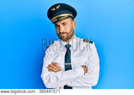 Handsome man with beard wearing airplane pilot uniform skeptic and nervous, disapproving expression on face with crossed arms. negative person.