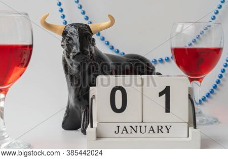 Statuette Of A Bull, Decorated With Beads. Wine Glasses In The Background. Selective Focus.