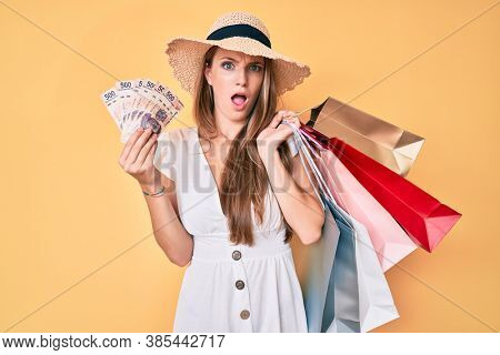 Young blonde woman holding shopping bags and mexican pesos banknotes in shock face, looking skeptical and sarcastic, surprised with open mouth