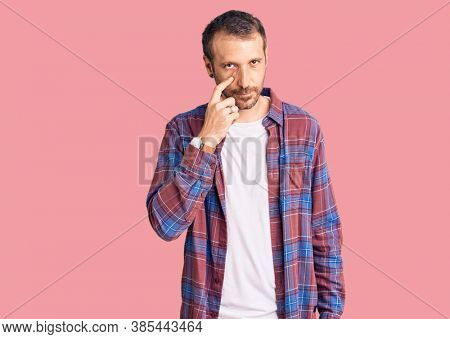Young handsome man wearing casual clothes pointing to the eye watching you gesture, suspicious expression
