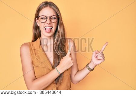 Young blonde woman wearing business shirt and glasses sticking tongue out happy with funny expression.