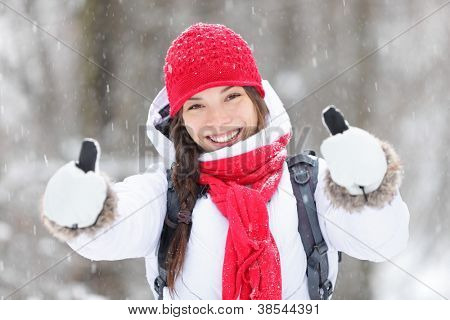 Happy young Asian woman with a beautiful vivacious smile dressed warmly in winter clothes standing outdoors in a snowstorm giving thumbs up gesture of approval poster