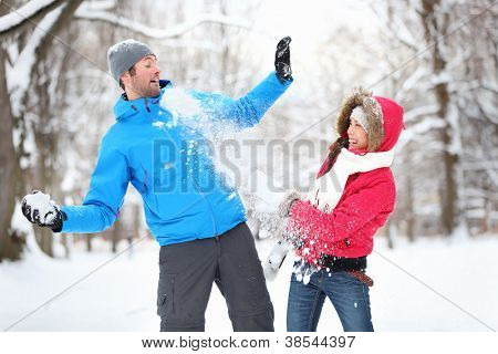 Carefree happy young couple having fun together in snow in winter woodland throwing snowballs at each other during a mock fight poster