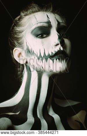 Portrait of a beautiful young woman with Halloween skeleton makeup over black background. Pumpkin queen. Day of The Dead.