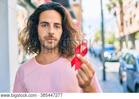 Young hispanic man with serious expression holding hiv awareness red ribbon at city.