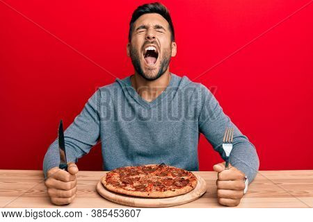 Handsome hispanic man eating tasty pepperoni pizza angry and mad screaming frustrated and furious, shouting with anger looking up.