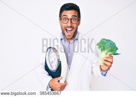 Young hispanic man as nutritionist doctor holding weighing machine and broccoli celebrating crazy and amazed for success with open eyes screaming excited.
