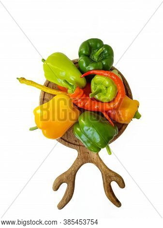 Bulgarian Pepper Yellow, Green And Red On A Kitchen Wooden Cutting Board On A White Background.