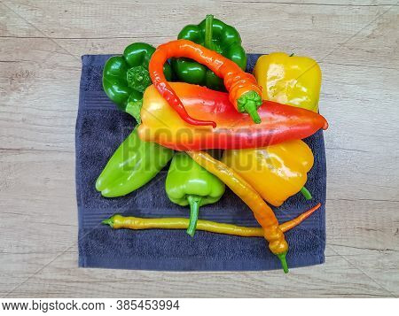 Bulgarian Peppers Of Yellow, Red And Green Are Scattered On The Working Kitchen Surface.