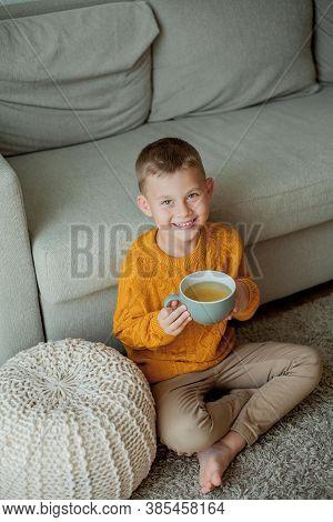 A Little Cute Boy In An Orange Sweater Is Drinking Tea. Cozy Portrait Of A Boy Sitting At Home. Fall