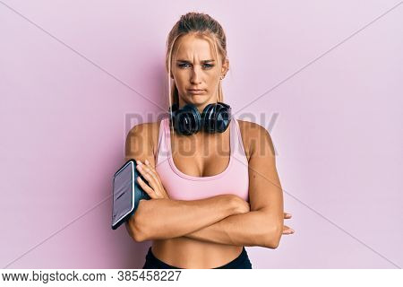 Young blonde woman wearing gym clothes and using headphones skeptic and nervous, disapproving expression on face with crossed arms. negative person.