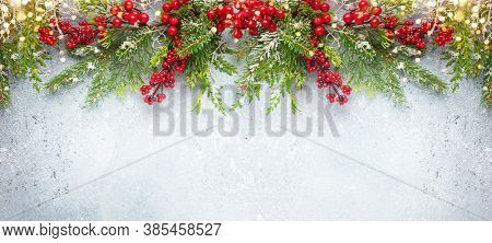 Christmas or winter background with a border of green  frosted evergreen branches and red berries on a grey vintage board.
