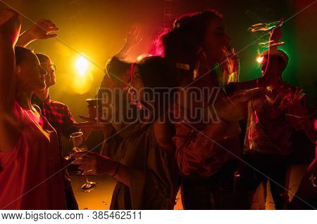 Youth. A Crowd Of People In Silhouette Raises Their Hands, Dancing On Dancefloor On Neon Light Backg