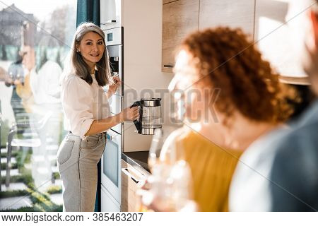 Woman Getting Ready To Prepare Hot Drinks For Guests